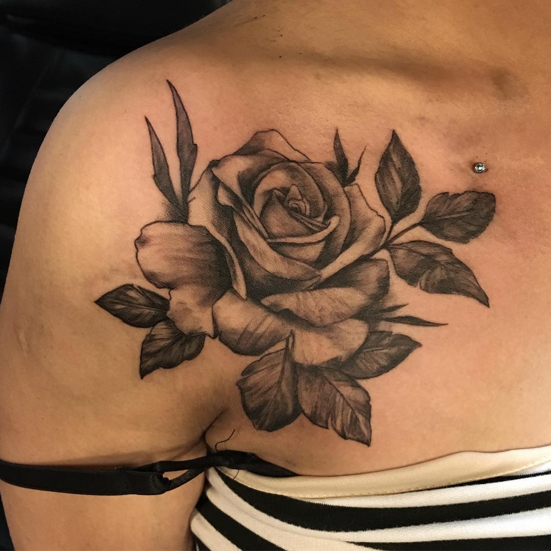 Rose tattoo in front of shoulder with leaves