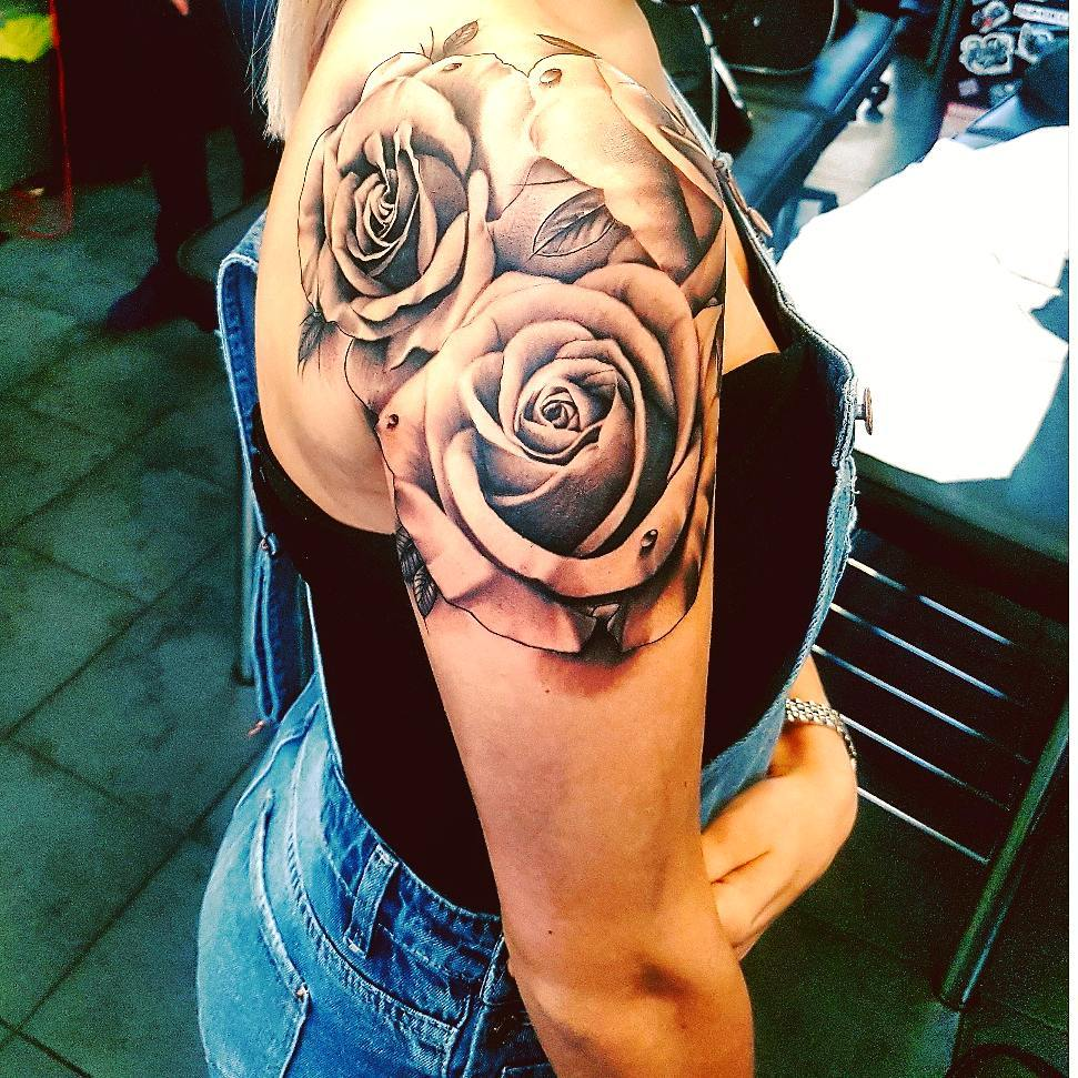 Top down look at a large rose shoulder tattoo
