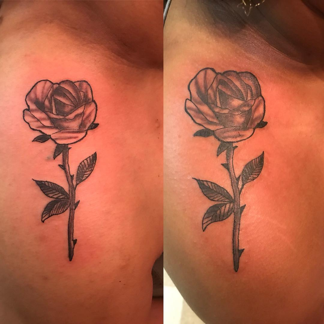 Full stemmed rose tattoo on back of shoulder