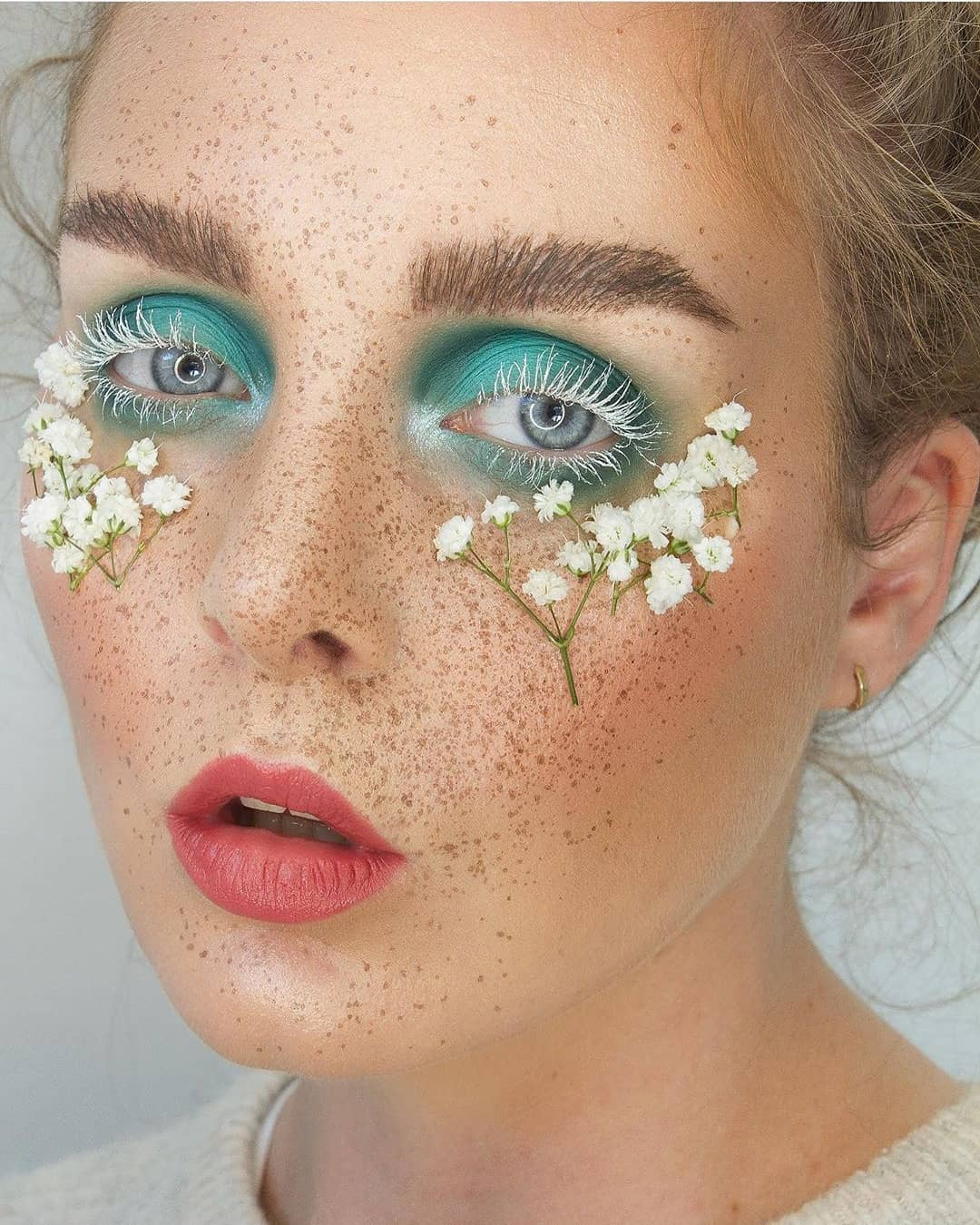 Teal eyeshadow, white lashes with Faux Freckles Makeup technique