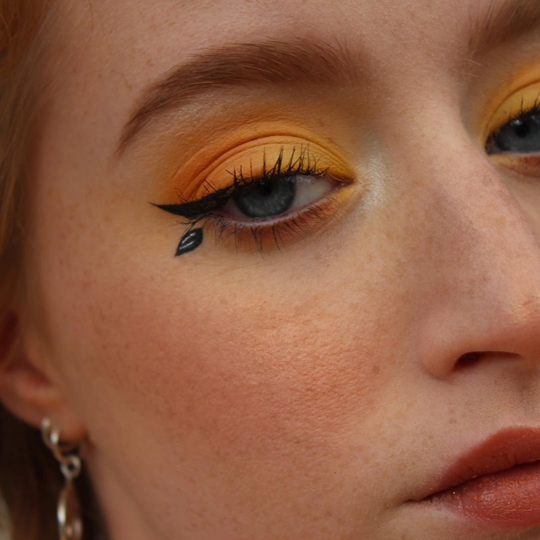 Orange eyeshadow with leaf as a makeup accent and winged eyeliner