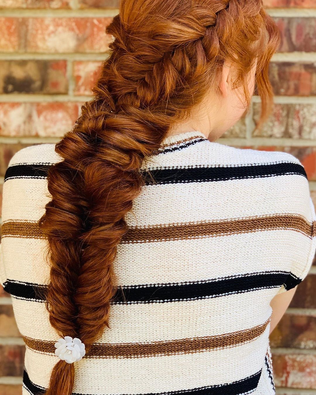 Fishtail boho braids pulled together in long red hair