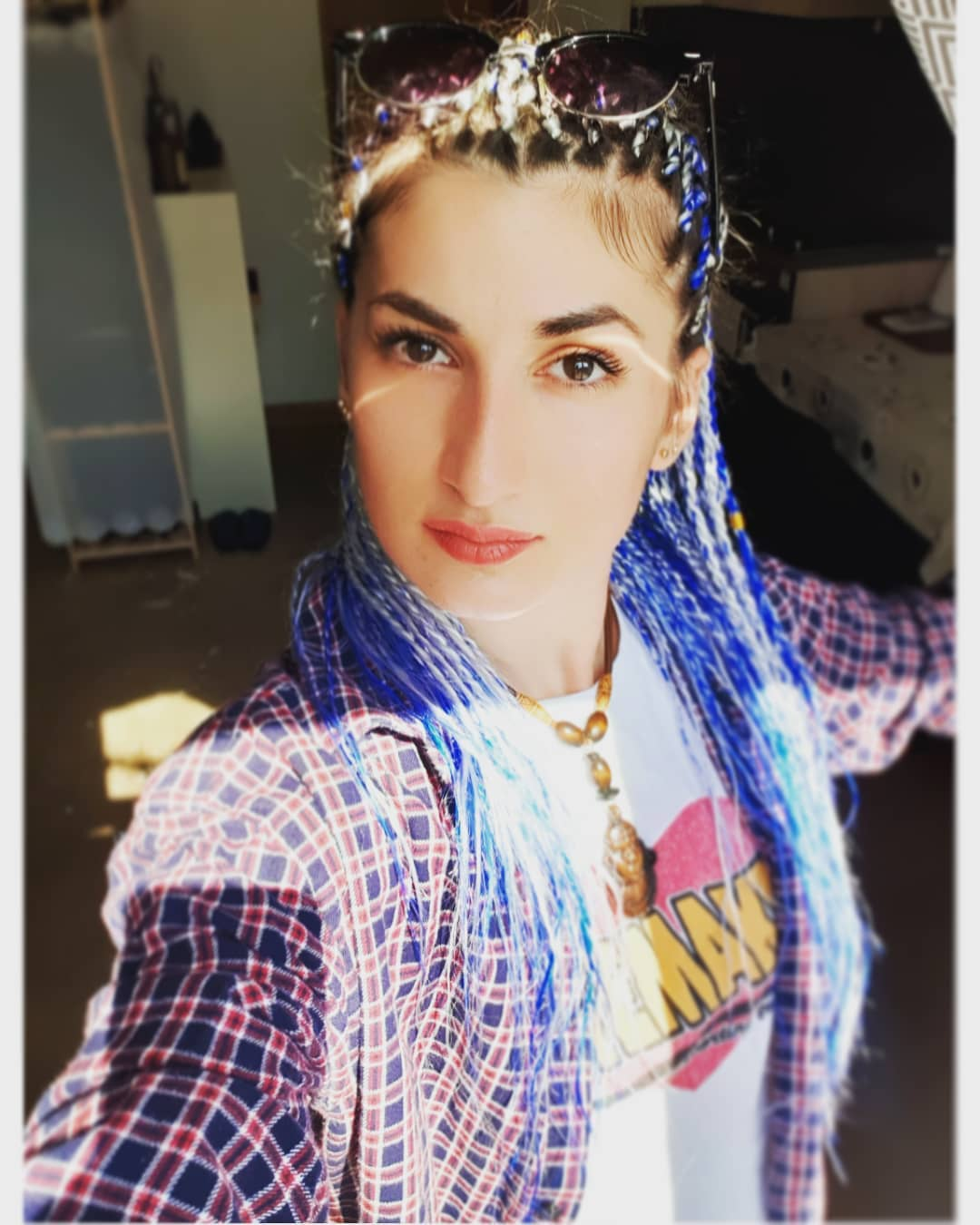 Girl wearing flannel shirt and senegalese twists with blue color