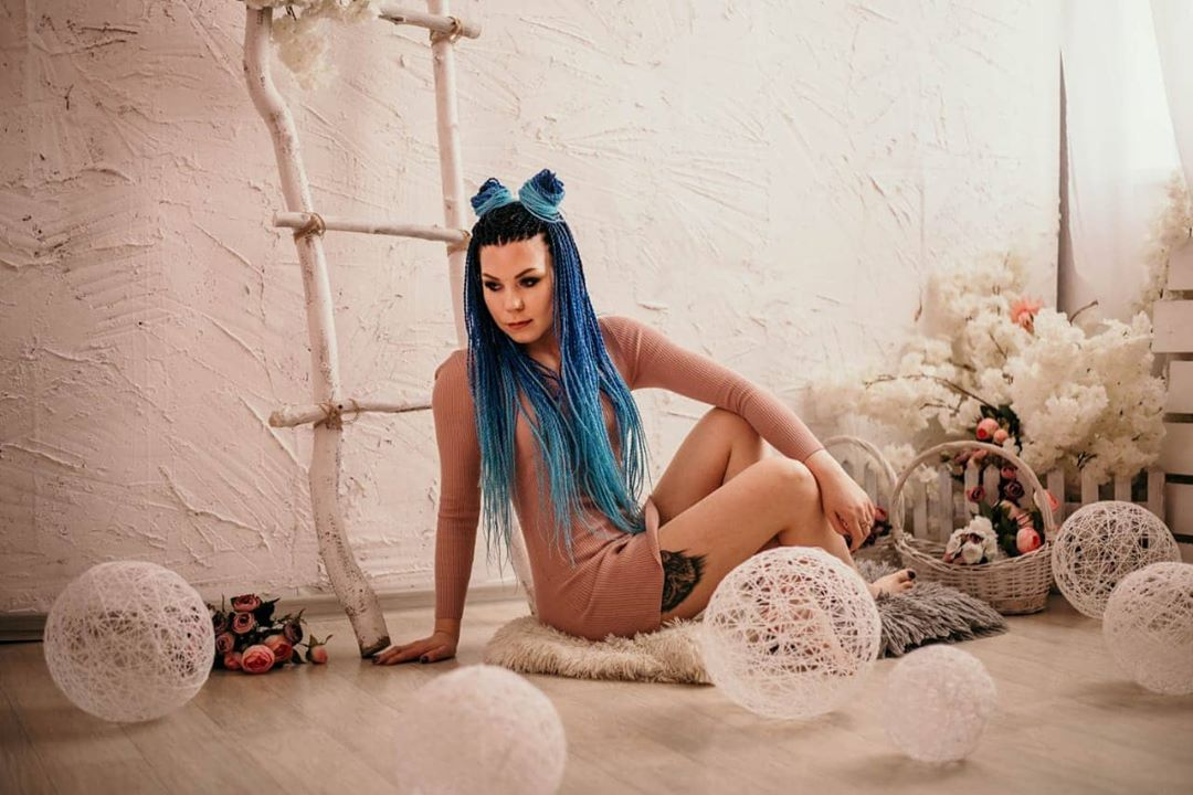 Blue colored braids with space buns